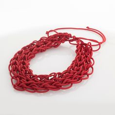 'Intreccio rosso' is an handmade necklace, made of cotton cable and nylons, plaited with fingers. The particular production makes this optional soft and light. 100% made in Italy. Weight: 58 gr.