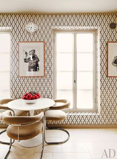 Black and white wallpaper in dining space with white table and chairs