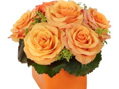 A wet floral foam container sports a cheerful array of tangerine colored  roses  that are set off by the green tones of the galax leaves and solidago.