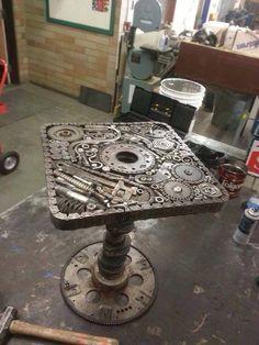 mesa de metal, con requechos, casi una escultura