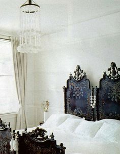 ornate antique black twin headboards used together to create a wicked king bed