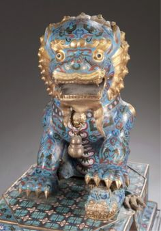 "Pair of Chinese cloisonne foo dogs.  Pair of two Chinese blue cloisonne foo dogs with gilt accents. Late 19th/20th century. With cloisonne bases on wooden stands. Without stands: 22""h x 13 1/2""w x 18 1/2""d."