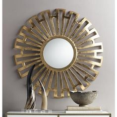 A hand-finished sunburst wall mirror with a convex metal frame in a bright gold finish.