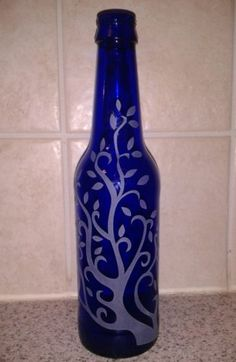 Etched Cobalt blue bottle recycled / repurposed. Can be used as a vase, candle holder, tiki torch or just sit in a window for decoration.