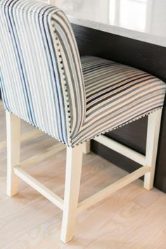 Classic ticking stripe upholstered bar stools echo the dark and light tones in the room and make for comfortable seating at the kitchen island.