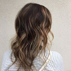 Medium waves are easy and effortless, but on fine strands they can appear somewhat stringy. By filtering in ribbons of light caramel into dark brown hair, you can define your waves and make them pop more.