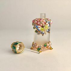 Beautiful glass perfume/oil bottle embellished with crystals, handpainted butterfly, and flowers. Seals tight. Measured approximately: 3 1/4 tall Weighs approximately: 4 oz Perfect Condition
