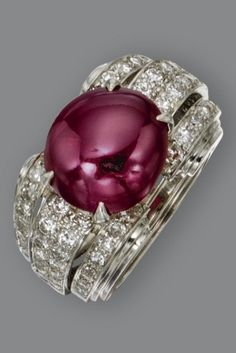 An Art Deco ruby and diamond ring, circa 1935. Set with an oval cabochon ruby weighing approximately 7.50 carats, flanked by rows of 48 single-cut and 16 round diamonds weighing approximately 1.10 carats, mounted in platinum, numbered. #ArtDeco #ring