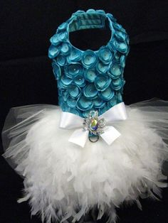 Blue Satin Rosette Dog Dress KO Couture Knock Out Fashion for Pets!  Mirror, Mirror on the wall. Whos the fairest dog of them all? DETAILS - Beautiful blue satin fabric - Bodice of dress is completely covered in handmade satin rosettes sewn on by hand - Swarovski crystals adorn the center of each rosette - Lined and interfaced for long lasting durability - Strong metal D-ring added for easy leash attachment - Long flowing white sparkle tulle skirt - Matching crystal pin adds the perfect…