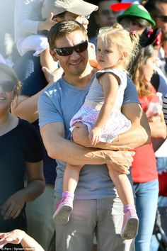 Happy times: The Hurt Locker star was seen cradling the tot as they took in the rides and sites in the park,