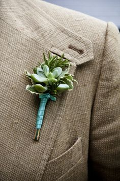 succulent boutonniere but with a purple ribbon.