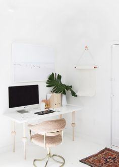 Bright white home office with an IKEA desk and a vintage chair