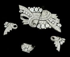AN ART DECO DIAMOND SUITE  Comprising a double clip brooch composed of two opposing scroll design panels pavé-set with circular-cut diamonds and pear shaped diamond highlights, with similarly-set earrings and ring en suite, circa 1930