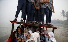 20150910 - Em meio a forte neblina, estudantes se equilibram no teto de um barco durante travessia do rio Musi, rumo à escola em Palembang, na ilha de Sumatra, na Indonésia. O país está investigando dez empresas após o agravamento dos incêndios florestais, que criaram uma espécie de cobertor de fumaça sobre sudeste da Ásia. PICTURE: Beawiharta/Reu
