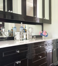 Black and white butler's pantry features mirrored upper cabinets and glossy black lower cabinets adorned with glass knobs paired with white a marble countertop and a black framed mirrored backsplash.