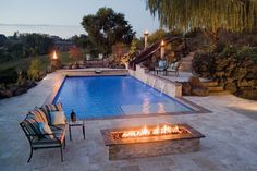 This poolscape features three separate bistro patio areas. Each nook offers a different view of the surrounding landscape and establishes a more intimate atmosphere. A firepit adds a cozy touch for summer nights spent al fresco. Photo courtesy of Rugged Class Waterfalls & Pools; Photography by Stephen K. Wolfe http://www.luxurypools.com/blog/entryid/90/poolside-living-patio-designs-ideas.aspx