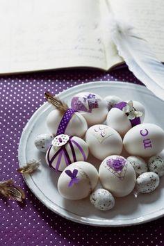 Des œufs de pâques décorés avec des rubans, des plumes, des boutons et des papiers blancs et violets