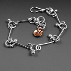 """This handmade silver bracelet is all handmade from the clasp, to the little balls of silver to the tiny, hand-stamped fleur de lis copper charm accent.Adjustable to fit wrists about 6-7"""" around but can be made in any size. Unique and fun - just like you. Comes in a gift box, ready to give or keep for yourself."""
