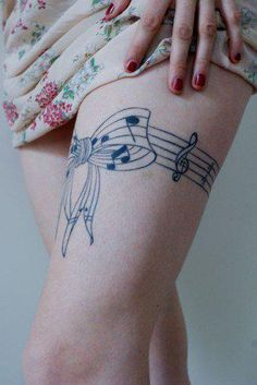 Thigh placement. Garter tattoo. Music note bow.