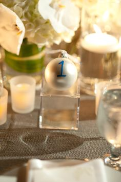 Cute custom white Christmas ornaments as table numbers for this winter wedding rehearsal Dinner at Max's Wine Dive in downtown Austin. Photography by Jenny DeMarco www.jennydemarco.com | Decor by David Kurio Designs