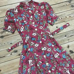 """{ Sold } 1930s cotton day dress with puff sleeves, little round collar, working pockets, original belt and pearl buttons. Floral print on a dark dusty pink background. Closes with 11 buttons all the way in the front. Great condition, some wear to the button holes. Bust 17"""", waist 12""""-14"""", hips 20"""", shoulders 13"""", length from shoulder to hem 39"""". Dm for more info!"""