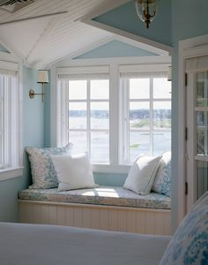 A light-filled window bench decorated in pale blue & white
