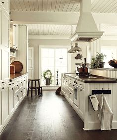 White walls kitchen-wood details. Contrasting floors, dark counters