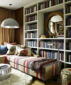 This is a great way to have a lot of books on selves without having it look cluttered and messy. The mirror in the middle makes all the difference.(I am kind of liking the striped pattern on the furniture).
