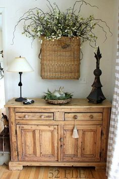 Large basket with flowers over a cabinet.