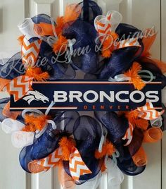 This is a blue deco mesh wreath accented with orange and white ribbon, white deco mesh and tubing. Denver Broncos sign also to accent. This is