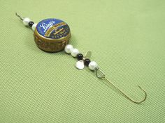 Bottle cap fishing lure made from two bottle caps and beads and one fish hook and one spinner