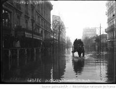 29-1-1910, rue de La Convention [inondations de Paris, 15e arrondissement, véhicule hippomobile et piétons sur les planches sur pilotis] : [photographie de presse] / [Agence Rol] - 1