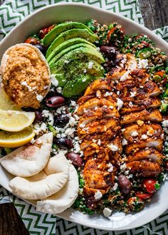 overhead of a salad loaded with pita, hummus, lemon wedges, avocado, chicken shawarma, and olives.
