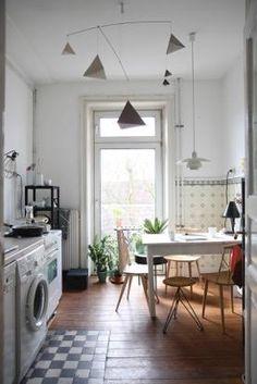 Wunderschöne Altbauküche mit hoher Decke. Einrichtungs-Idee für eine schöne Küche mit Waschmaschine, Dielenboden, Esstisch und Stühlen.