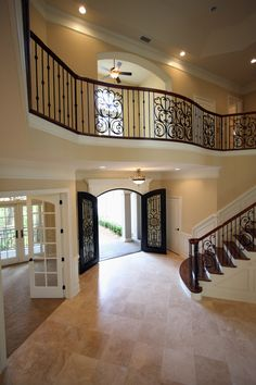 amazing open foyer with beautiful stair case and balcony, black iron scrollwork, accent lighting, neutral tile, french doors... by the BEST custom construction contractor in central Florida | www.allinconstruction.com