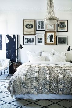 Dreamy gallery wall above the bed, sparkling sequined Moroccan wedding blanket, classic piped white shams, and black and white photographs and abstract art. Love!