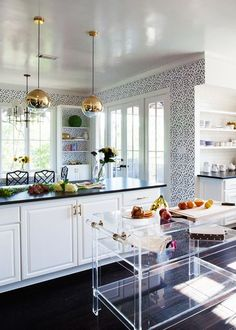 an acrylic island in a bright kitchen with brass details  featured on lonny magazine | via coco+kelley
