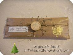 Pacco regalo con cartoncino ondulato. Decorazione con spago, alberello di natale dorato e una corteccia di legno