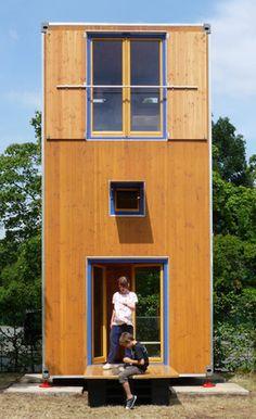 HomeBox1 ist ein hölzerner Wohnturm, der nicht größer ist als ein handelsüblicher Frachtcontainer, aber alle essenziellen Anforderungen an ein Haus erfüllt.