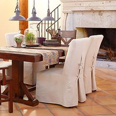 rustic Italian inspired dining room table with slipcovered chairs