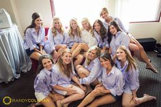 Candid bridesmaids in monogrammed lavender men's shirts with bride in white shirt