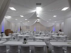White Chair Covers, White Table Linens, White Ceiling Drape, White Pipe & Drape with Blue Uplights (hollywood package), Candle Bowls, Round Mirrors, Votives and a Floating Candle, Black Lantern, Square Mirrors, Votives and a Pillar Candle at Gustavus Lutheran Church by Deckci Decor