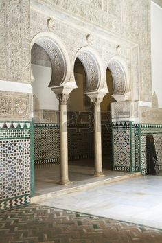 An interior courtyard showing arches and decorative wall tiles in the Reales Alcazares Seville Spain Stock Photo