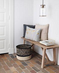 Déco et coussins aux teintes beiges avec un petit banc en bois et suspension design