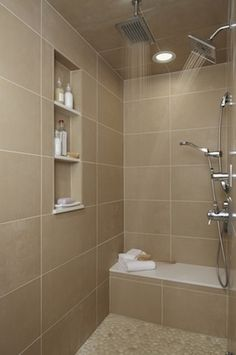 Contemporary shower with in shower seating and shelving.