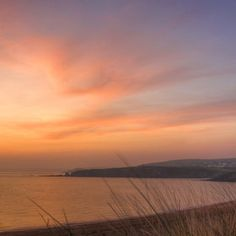 """""""The glow of one warm thought is to me worth more than money.""""    Thomas Jefferson    Sunset afterglow in the high-altitude clouds above Thurlestone Bay. Looking from South Milton Sands – with Burgh Island in Batham Bay behind the first headland."""