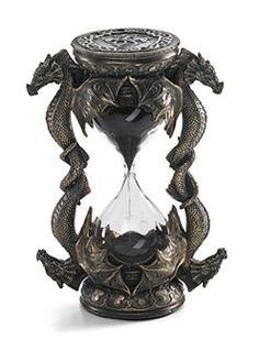 """Dragon Hourglass Pairs of patient dragons frame this hourglass, as the black sands count the minutes - what happens next, the dragons will not say. 6"""" tall bronzed resin hourglass marks five minutes of time."""