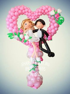 Cute wedding balloon decor: bride and groom sitting happily in a pink balloon heart frame.