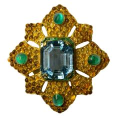 A Gracious Aquamarine Brooch by Van Cleef & Arpels during the late 1960s, presenting a very fine aquamarine weighing 35,4 cts, decorated by four cabochon emeralds and by a pavè of citrines, all mounted in 18kt yellow gold.