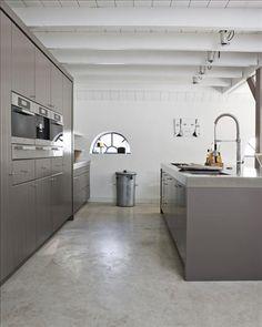Lantligt rustikt och ultramodernt på samma gång. Kökets olivtonade inredning är specialbyggd för huset och harmonierar fint med det råa betonggolvet. Kaffemaskin, ugn och micro är integrerat i skåpen, och spishällen elegant nedfälld i bänkskivan av rostfritt stål.